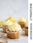 Small photo of Lemon and poppy seed cupcakes with cheese cream frosting and lemon and lime zest on a rustic white wooden table