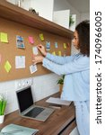 Small photo of Young african american woman pin weekly planning sticker on mood board at home office. Black girl put post it sticky note memo on board to organize work goals, self organization concept. Vertical