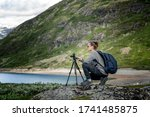 Young woman traveler professional photographer takes a picture of the landscape on the camera on a tripod, Norway, beautiful northern nature - stock photo
