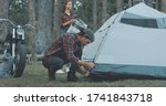 Hiker camping in forest. Guy biker sets up tent in woods. Handsome young man tourist puts hiking backpack. Countryside lifestyle scene. - stock photo
