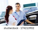 young man choosing car at salon ... | Shutterstock . vector #174213902