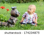 Stock photo little boy making funny faces on a statue in a garden 174234875