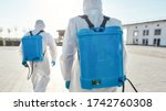Small photo of Sanitization and disinfection of the city due to the emergence of the Covid19 virus. Specialized team in protective suits and masks with backpack of pressurized spray disinfectant. Rear view