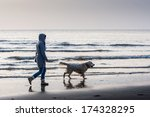 Stock photo woman walking with dog on the beach atlantic ocean netherlands europe 174328295