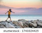 Boy Walking On Rocks At Sunset...