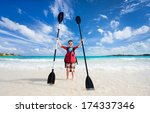 Little boy holding kayak paddles at beach - stock photo