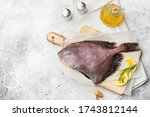 Small photo of Dory's raw fish is on a wooden Board on the light gray kitchen table. Dori fish close-up. Top view with space for text