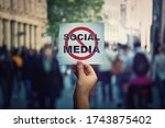 Small photo of Social media censorship, political war between US president banning social networks. Hand holding a banner with forbidden sign over a crowded street background. Internet communication risk concept.