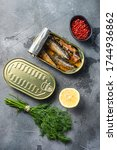 Canned saury, open and closed can with wfresh herbs, peppercorns, lemon, on grey concrete stone background top view