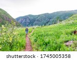 Morning on path road on Conundrum Creek Trail in Aspen, Colorado in 2019 summer near trailhead with man walking - stock photo