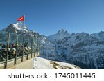 Grindelwald, Switzerland - December 30, 2019: People enjoying beautiful views on Bernese Alps from restaurant on First above the Grindelwald in Switzerland during sunny day in December 2019 - stock photo