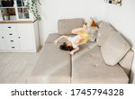 Small photo of Beautiful little toddler tumbling on sofa at home. Child Learn To Tumble. Tumbling Tutorial. Gymnastics at Home, Tricks