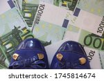 Woman's blue ballet Shoes stepped on the money 100 Euro bills. Money wasting and spending concept. - stock photo