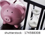 Small photo of Pink ceramic piggy bank with an hour glass, conceptual of time running out to save for your retirement, a nest egg or to meet your dreams