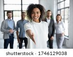 Small photo of Head shot portrait smiling African American businesswoman offering handshake, standing with extended hand in modern office, friendly hr manager or team leader greeting or welcoming new worker