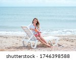 Woman Sitting On The Beach Wit...