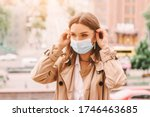 Small photo of Beautiful stylish girl wear medical face mask on sunny city street. Young elegant happy hipster woman put on protective face mask outdoors. Urban fashion outfit, lifestyle. COVID-19 quarantine, travel
