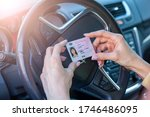 Small photo of Getting a driver's license, female hands show US driving license, amid the steering wheel of a car