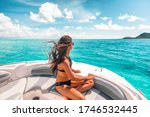 Small photo of Luxury yacht woman enjoying freedom on deck in the wind relaxing on high end boat summer vacation trip upscale lifestyle of young rich people. Elegant black bikini, long hair and sun tanned body.