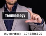 Small photo of Businessman on a black background holds an icon with the text Terminology