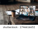 Small photo of Virtual meeting online. Video conference by laptop. Online business meeting. On the laptop screen, people who gathered in a video conference to work on-line, near stands a cup of coffee