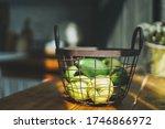 Ripe raw fresh green avocado and apples in metal basket in kitchen, hard sun light - stock photo