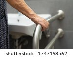 Small photo of Asian senior or elderly old lady woman patient use toilet bathroom handle security in nursing hospital ward : healthy strong medical concept.