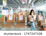 Small photo of Asian female tourist wearing mask using mobile phone searching airline flight status and sit social distancing chair in airport during coronavirus or covid-19 virus outbreak a new normal concept