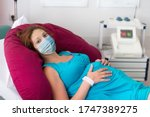 Pregnant patient in face mask in a hospital at doctor visit during coronavirus outbreak. Mother giving birth to baby in covid-19 lockdown. Pregnancy examination. Expecting woman in labor and delivery. - stock photo