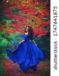Romantic portrait of a beautiful young girl in a long ultramarine blue dress running away on the background of an autumn рark with red leaves