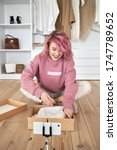 Small photo of Happy hipster gen z teen girl fashion social media channel blogger pink hair wear hoodie record unboxing vlog on phone video camera tutorial sit on floor open online store clothes order box, vertical.