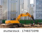 Heavy excavator in a working high frequency hydraulic vibratory mounted pile driver on road against the background of residential multi-storey buildings - stock photo