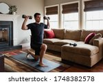 Fit man exercising at home with ...
