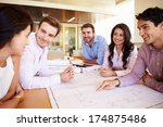 Small photo of Group Of Architects Discussing Plans In Modern Office