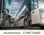 Satisfied Caucasian Bus Driver in His 30s Leaving Coach After Hard Day on the Road. Intercity Public Transportation. Early Evening Summer Hours. Bus Driving. - stock photo