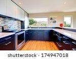 Stock photo elegant kitchen room with black wood storage combination with stoned backsplash and decorative vase 174947018
