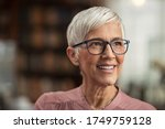 Small photo of Portrait of smiling mature woman with spectacles in library looking away. Senior librarian standing in reading hall and thinking. Old beautiful lecturer contemplating. Future and vision concept.