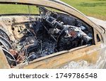Burnt out car in field, close up through drivers window. Stolen car dumped in agricultural area - stock photo