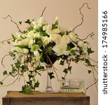 Small photo of Ranunculus,Iris, eryngium, ivy, ammi visnaga, corkscrew, hazel, in a bouquet