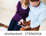 Young hugging  couple sitting on a sofa and using a digital tablet - stock photo
