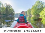 Young Girl Paddles In A Red...