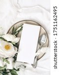 Small photo of Festive summer wedding scene. Marble table setting with cutlery, olive branches, white peony flowers, stoneware plate and silk ribbon. Blank restaurant menu card mockup. Flat lay, top view, vertical.