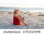 Small photo of Happy attractive Mature woman in red dress enjoying outdoors and freedom on the beach, open arms outstretched in hope after coronavirus quarantine eased. Back to life, outdoors and new normal concept.