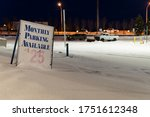 """""""Monthly parking available $25"""" sign in a car park at night during winter. Taken downtown in Anchorage, Alaska; W 3rd Avenue. Road in the back with cars passing, others are parked in the empty place."""