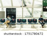 Small photo of Social distancing, two men wearing face mask sitting keeping distance away from each other to prevent covid19 infection during pandemic. Empty chair seat red cross shows avoidance in airport terminal.