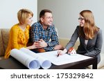Couple meeting an architect to discuss the blueprints - stock photo