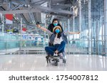 Small photo of Teen lovers wear a mask to protect against Corona virus. covid19 disease, sitting on a trolley luggage, cheerful fun enjoy to travel at the airport. New normal ,Vacation and travel concept