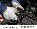 Small photo of Check engine ignition system and change ignition coil. Car care service. Replacing ignition coil and spark plugs. Car mechanic fixing ignition coil on gasoline engine.