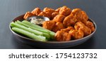 Small photo of plate of boneless chicken wings with buffalo sauce and celery sticks