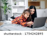 Small photo of Friendship of mom and her cute little daughter. They wallow at home on the floor in casual clothes and shopping online together using a laptop. They buy new toys for pretty little girl
